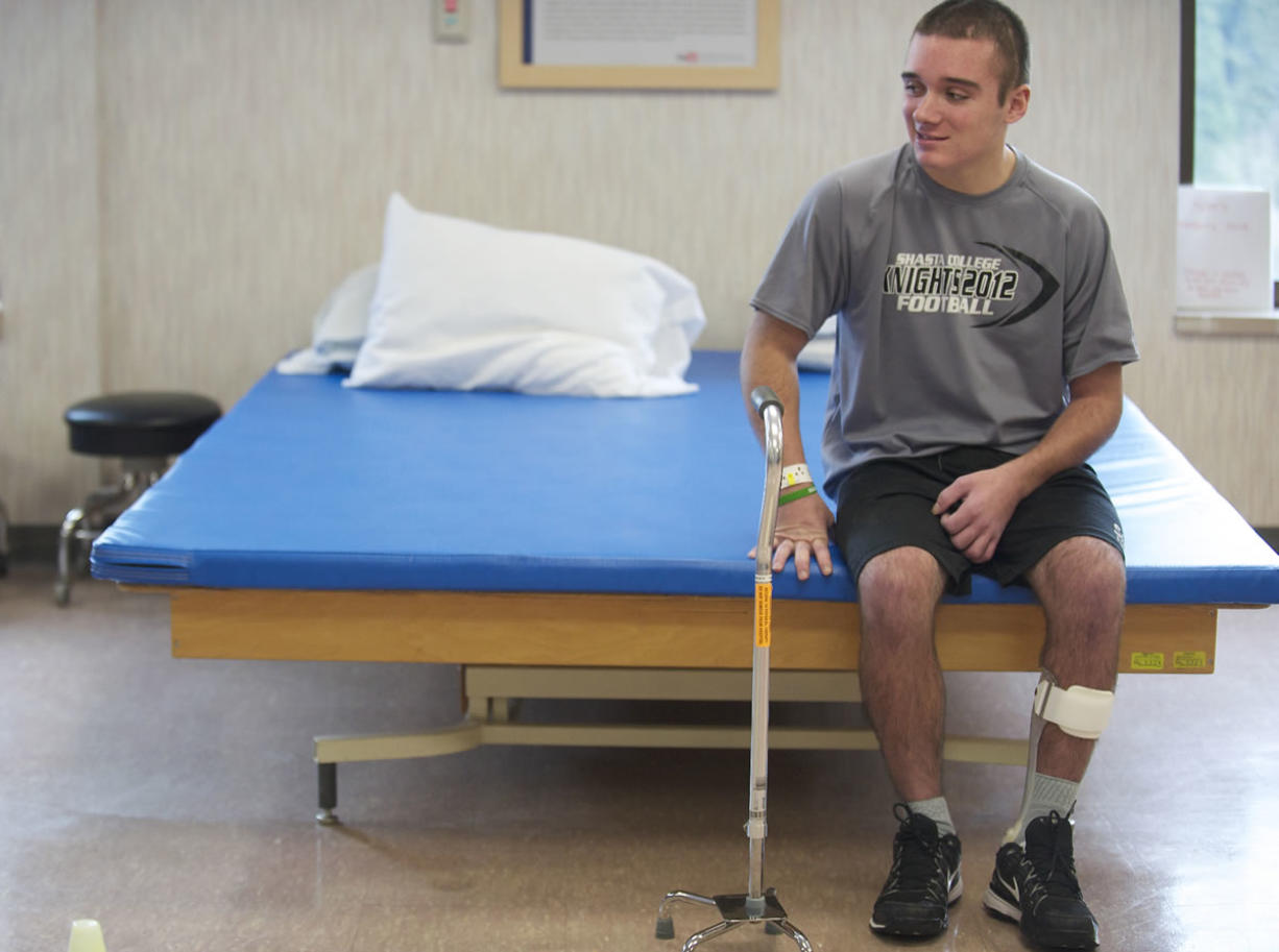 Tyler Burton, who suffered a brain injury in an assault in California last year, rests during a physical therapy session at PeaceHealth Southwest Medical Center on Monday.