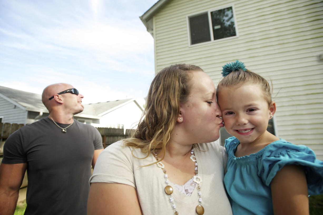 Brynley Verbeck, 4, shown with her mom, Jen Verbeck, fell out of her second-story bedroom window and was caught by attentive neighbor Nathaniel Forest, left. Forest scaled his backyard fence when he heard Brynley's screams.