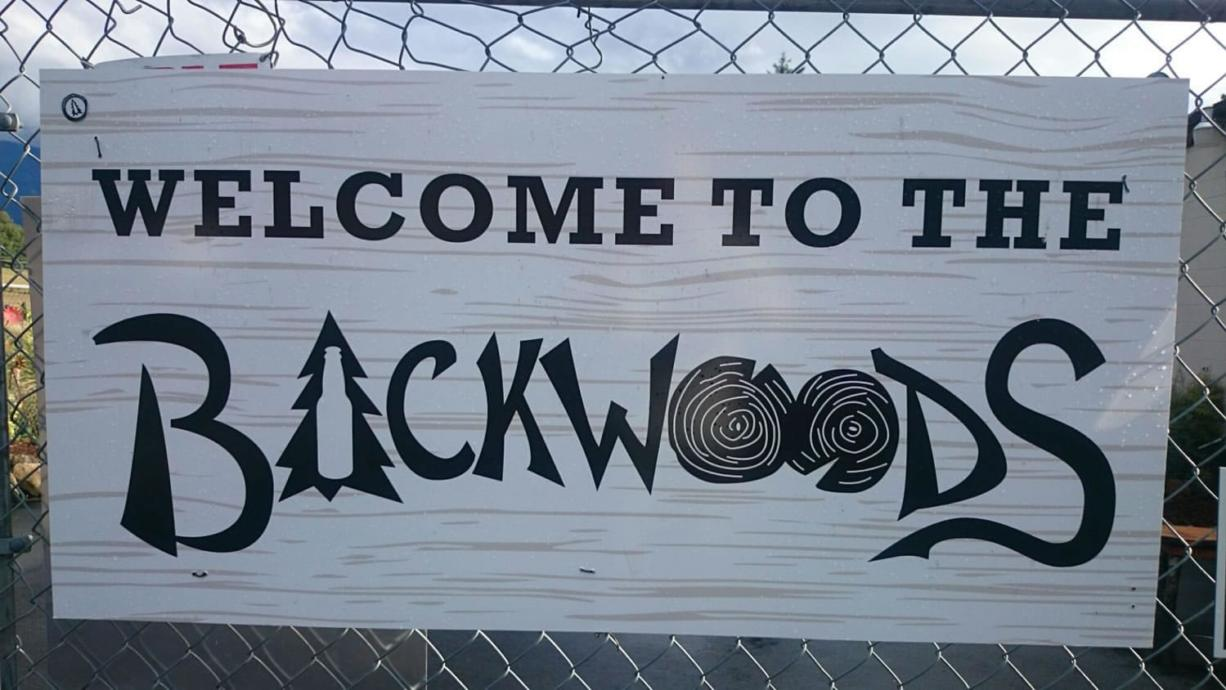 A sign hangs on the fence surrounding Backwoods Brewing's patio in Carson. The three-year-old brewery in the Columbia River Gorge is expanding so rapidly that production is moving to the Port of Skamania in Stevenson.