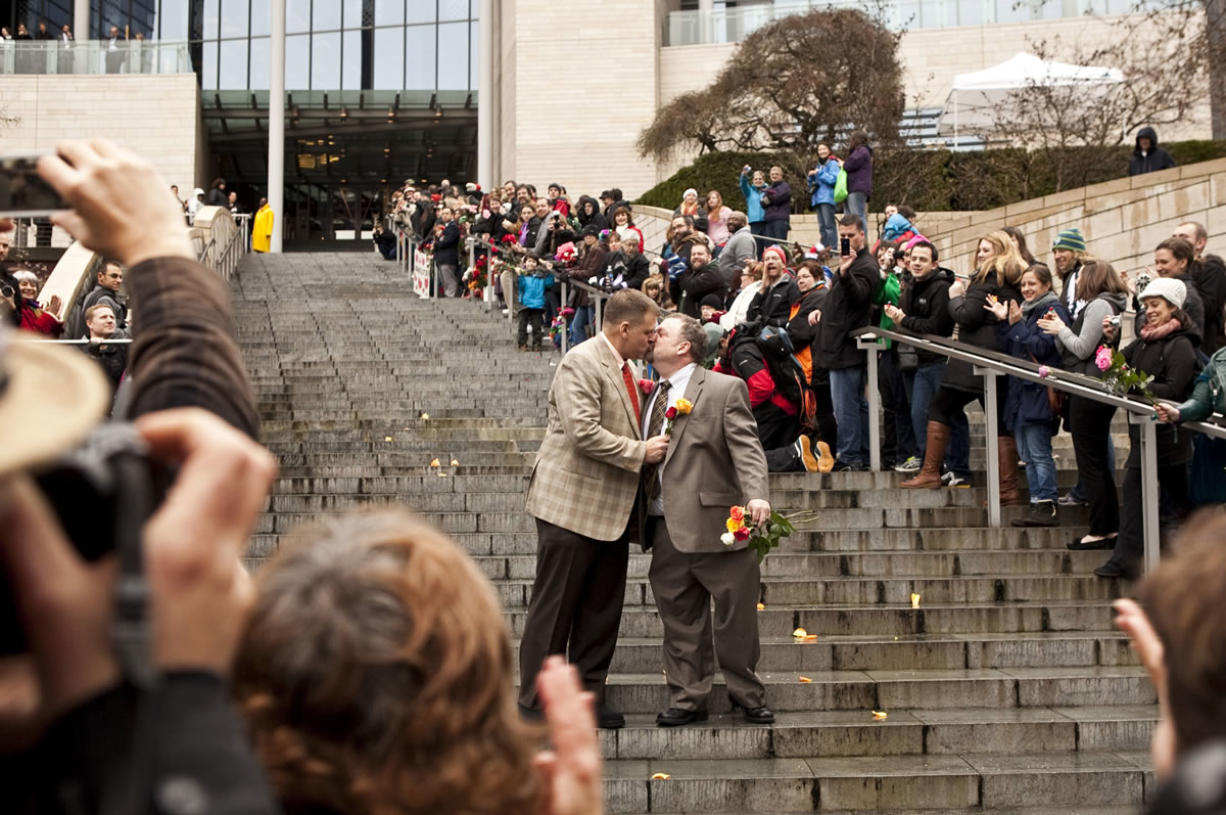 Brad McCanta, 48, left, and Jay McCanta, 52, both of Seattle, share a kiss on the steps of Seattle City Hall after being married Dec.