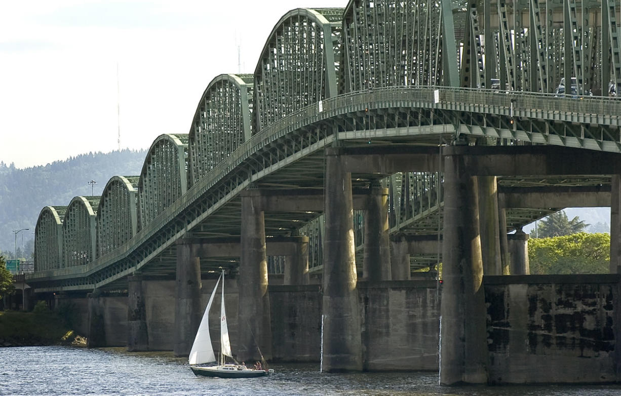 A sailboat passes under the Interstate 5 Bridge.