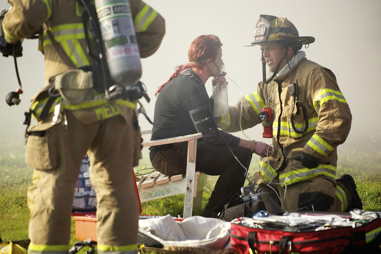 A firefighter with Clark County Fire District 6 assist an occupant of a duplex which caught fire in the Fruit Valley neighborhood Tuesday in Vancouver.
