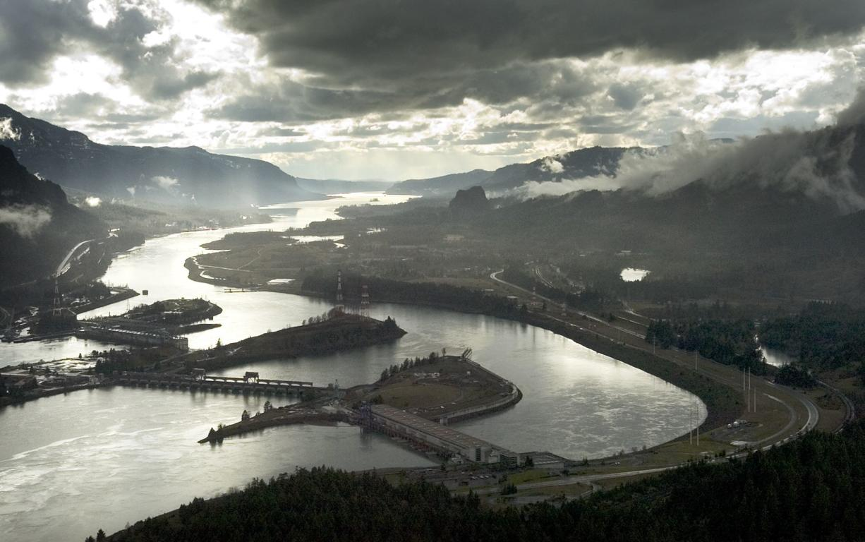 This aerial photograph of the Columbia River Gorge from 2006 shows the view looking west with Bonneville Dam in the foreground.