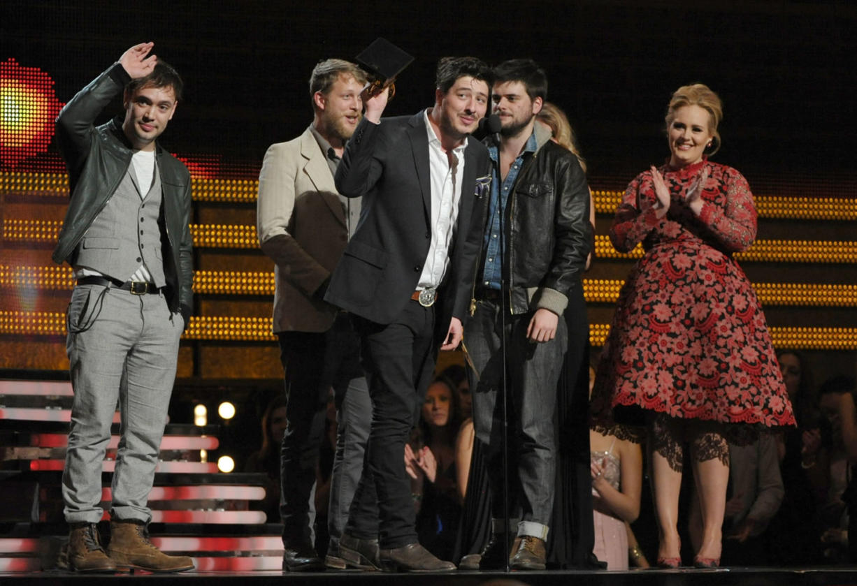 """Mumford & Sons, from left, Ben Lovett, Ted Dwayne, Marcus Mumford and Country Winston Marshall accept the award for album of the year for """"Babel"""" at the 55th annual Grammy Awards on Sunday in Los Angeles. Looking on from right is presenter Adele."""