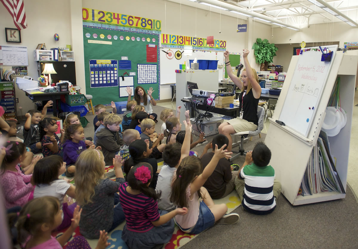Becky Kornell, right, welcomes kindergartners to her class this morning on the first day of school at Lincoln Elementary.