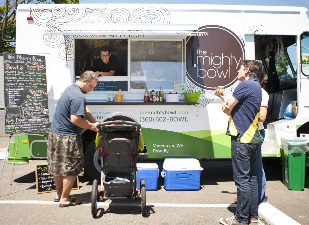 Customers gather at The Mighty Bowl, the first mobile food truck in Vancouver, at the intersection of East 22nd and Main streets at lunch on Wednesday.