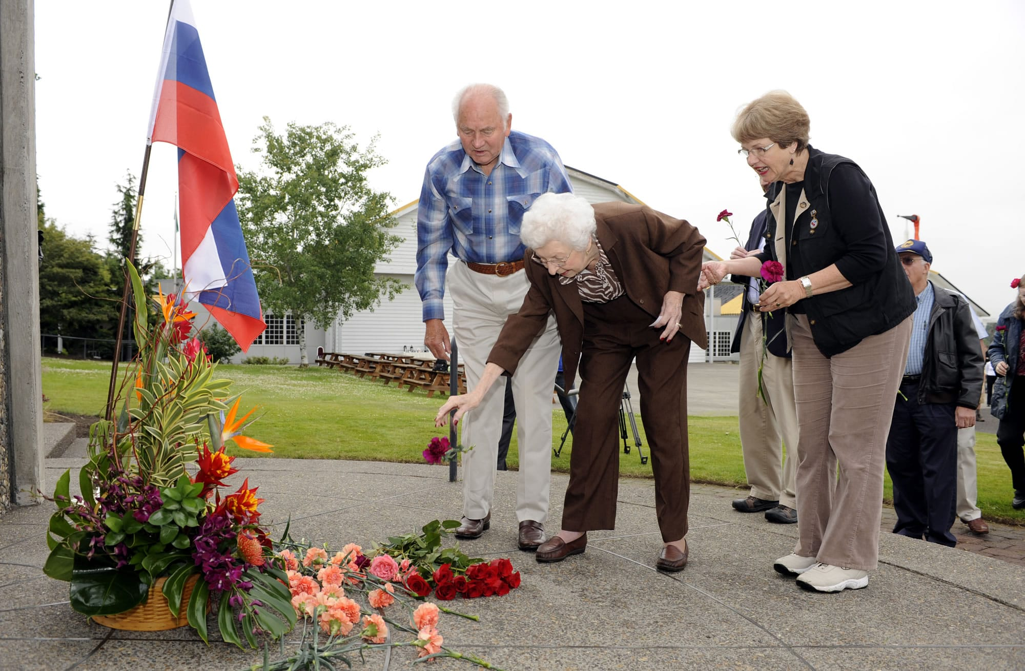 Former State Rep. Val Ogden, center, with Robert Buker, left, and Gayle Rothrock, place flowers at the Transpolar Flight Monument on Wednesday.