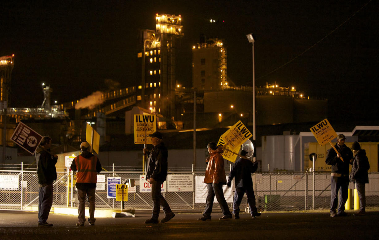 ILWU workers picket Wednesday evening in front of the Port of Vancouver's Gate 2 with grain terminals in the background.