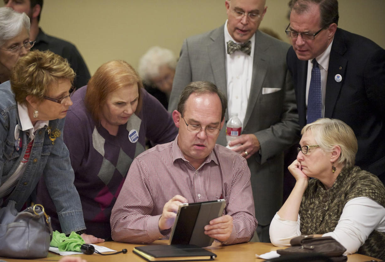 Vancouver City Councilor Jack Burkman, center, displays election results at Clark College's Gaiser Hall.