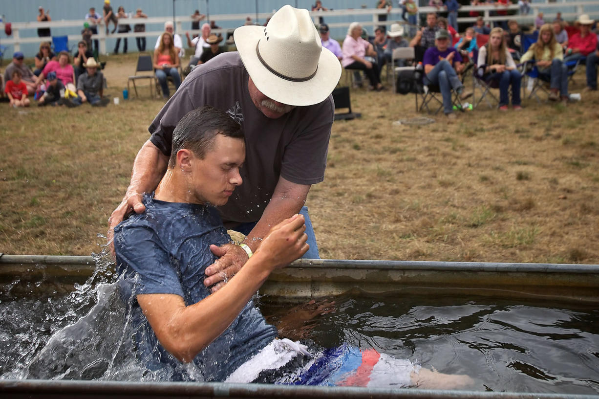 Using a horse trough, Larry Cutler baptizes Daniel Sage at the conclusion of the camp at the Vancouver Saddle Club on Aug. 15.