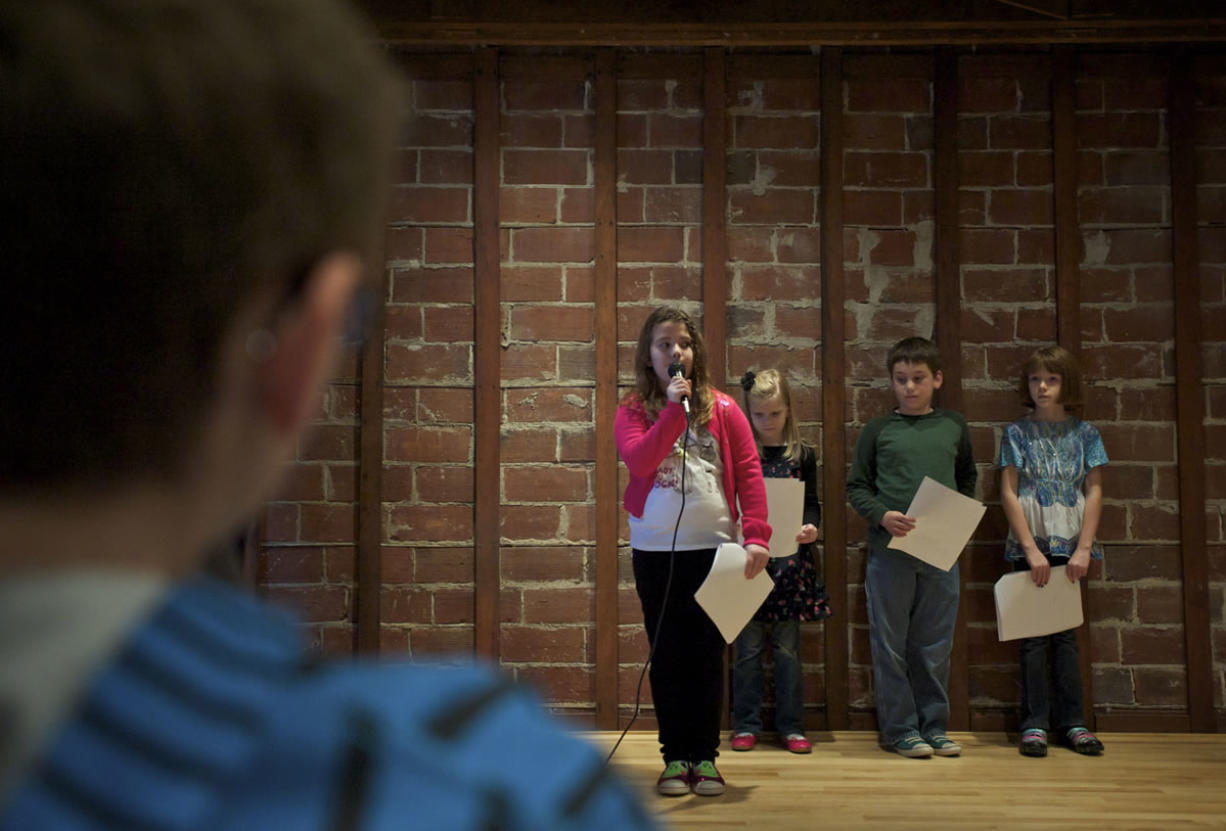 """Kailie Morrill recites her haiku, """"Cake,"""" while fellow Image Elementary School third-graders wait their turn Sunday. They are from left, Casey Logan, Preston Pickrell and Katelyn McCuistion."""
