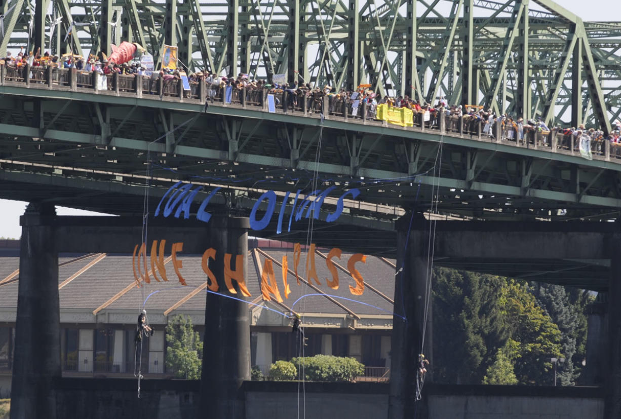 Three protesters on ropes lower a banner under the bridge supports as hundreds of protesters cross the Columbia River in support of an amphibious demonstration at the Interstate bridge against proposed fossil fuel facilities in the Northwest, in Vancouver, Wa., Saturday July 27, 2013.