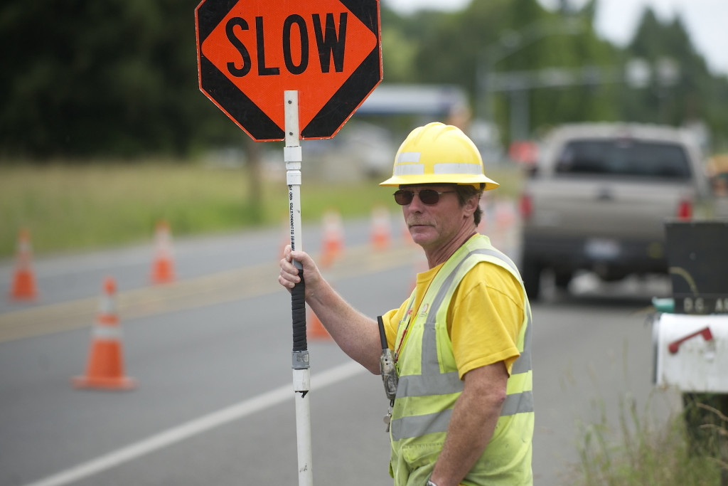 Flagger Rusty Goodson directs traffic near a utility works project on Northeast 72nd Avenue.