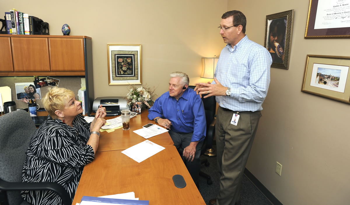Cyndi Romine, left, talks with Steve Johnson, the organization's marketing director, and husband, Greg Romine, in her office at Called to Rescue in east Vancouver on Thursday afternoon.