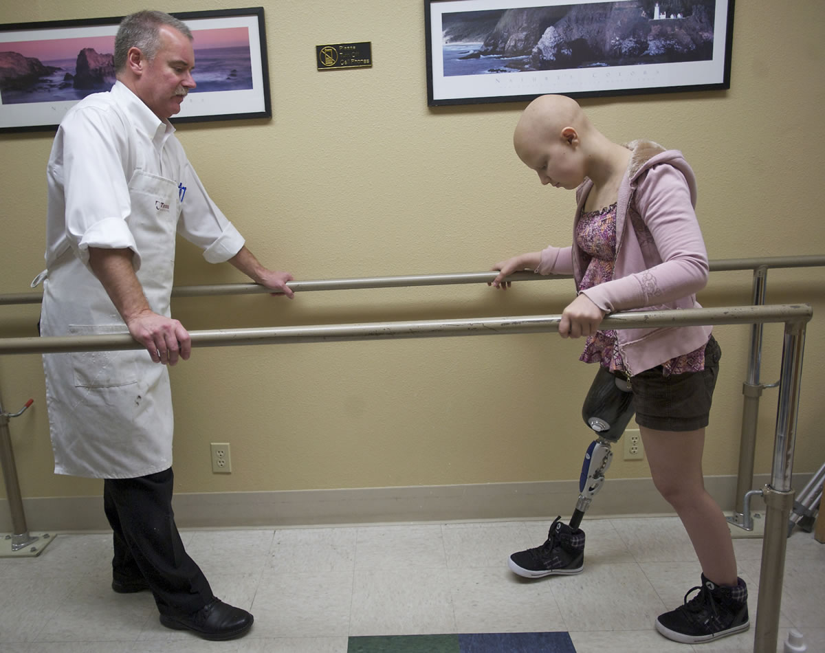 Caitlyn Lippolis, 12, takes her first steps with a prosthetic leg at Artisan Technologies in Tualatin, Ore., last month. Warren Mays, left, is president of Artisan Technologies, which constructed the leg.