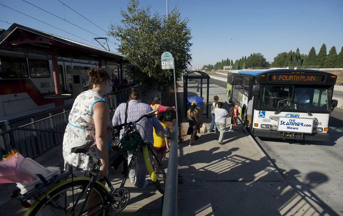 Commuters exit the MAX train at the Delta Park/Vanport Transit Center and head for a C-Tran bus Sept.