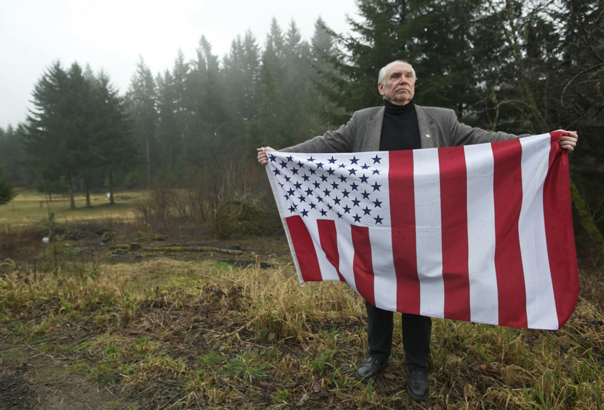 """David Darby, a follower of the Sovereign Citizens movement, holds a flag on his Amboy property. Darby says that to him the flag represents """"freedom and our constitutional rights."""""""