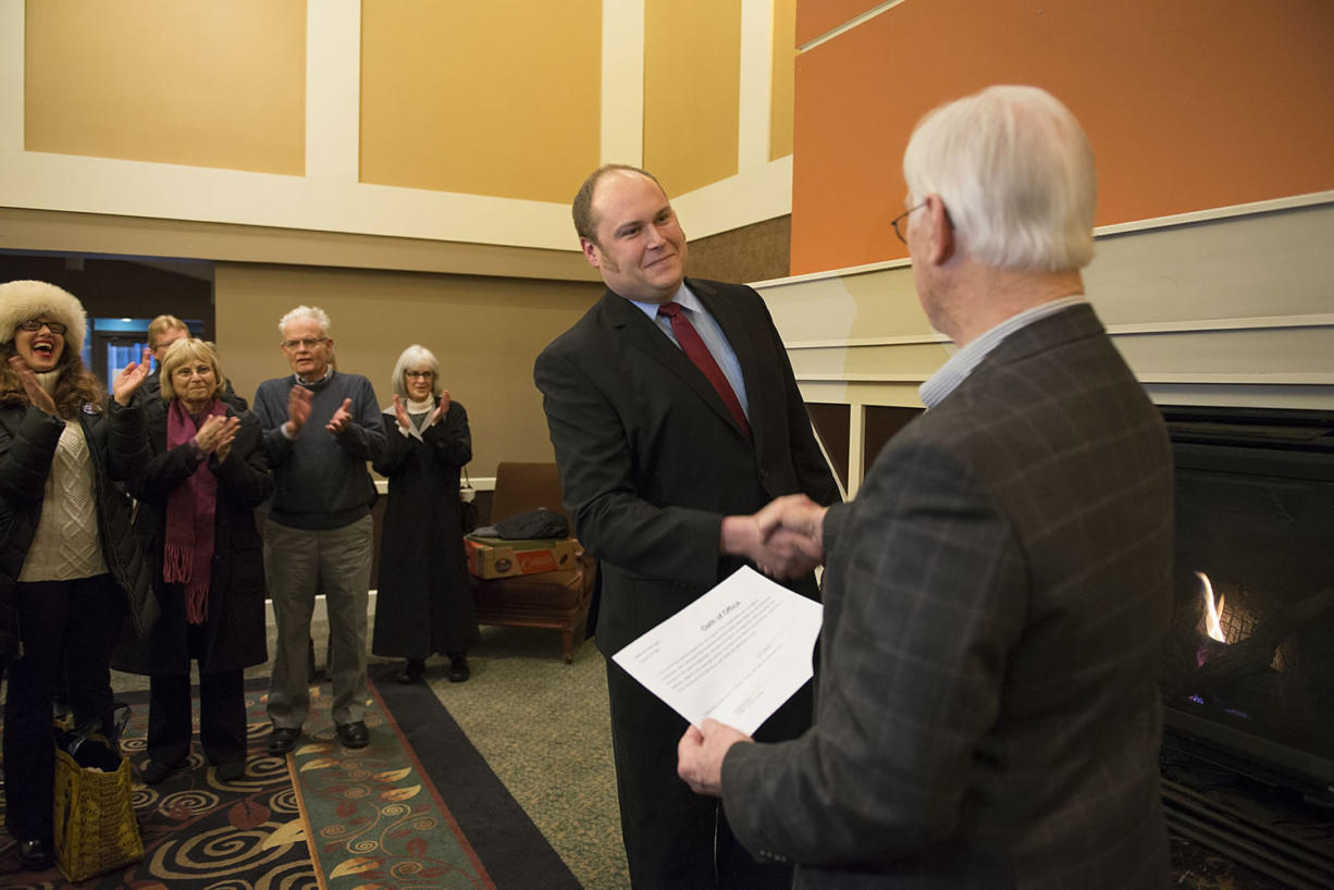 Newly elected Port of Vancouver Commissioner Eric LaBrant, center, is sworn in to office by Commissioner Brian Wolfe, a notary public, on Monday afternoon at the former Red Lion Hotel Vancouver at the Quay at the Port of Vancouver's Terminal One site.