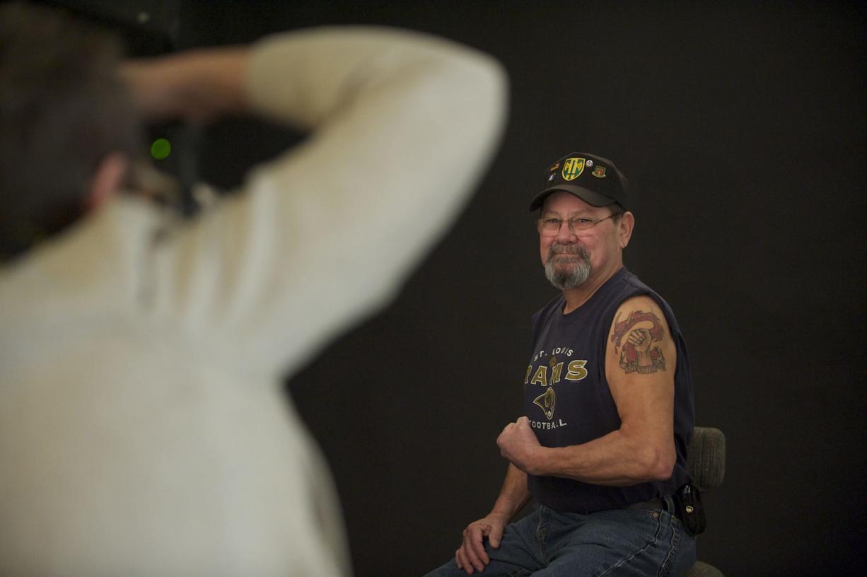 U.S. Army veteran Richard Alvarez flexes as Kate Singh takes a photograph for an exhibit of military-related tattoos.
