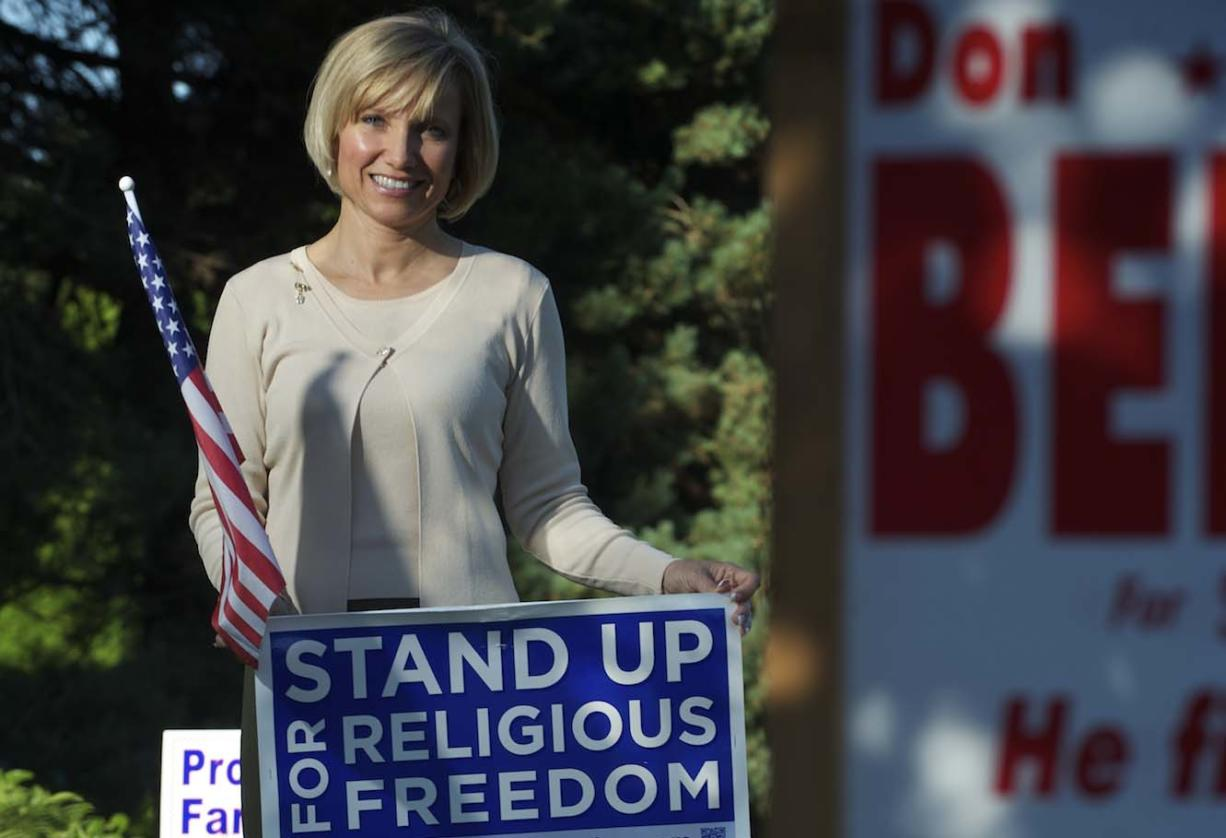 Lisa Schmidt stands Wednesday evening amid the yard signs in the front yard of her Ridgefield home.