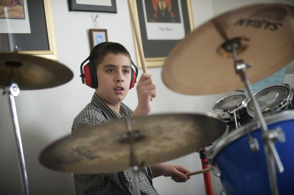 Ian Engelsman, 12, plays the drums in his family's home in Vancouver on Thursday.