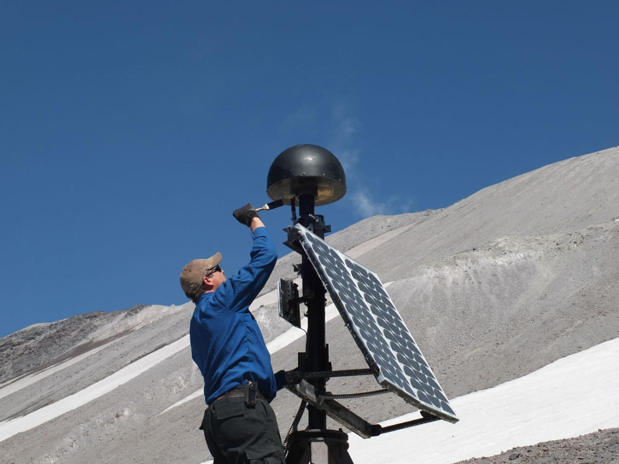 Cascades Volcano Observatory scientist Ben Pauk applies protective paint to a GPS antenna on Mount St. Helens. Researchers have spent recent weeks upgrading the monitoring equipment used to collect data from the volcano.