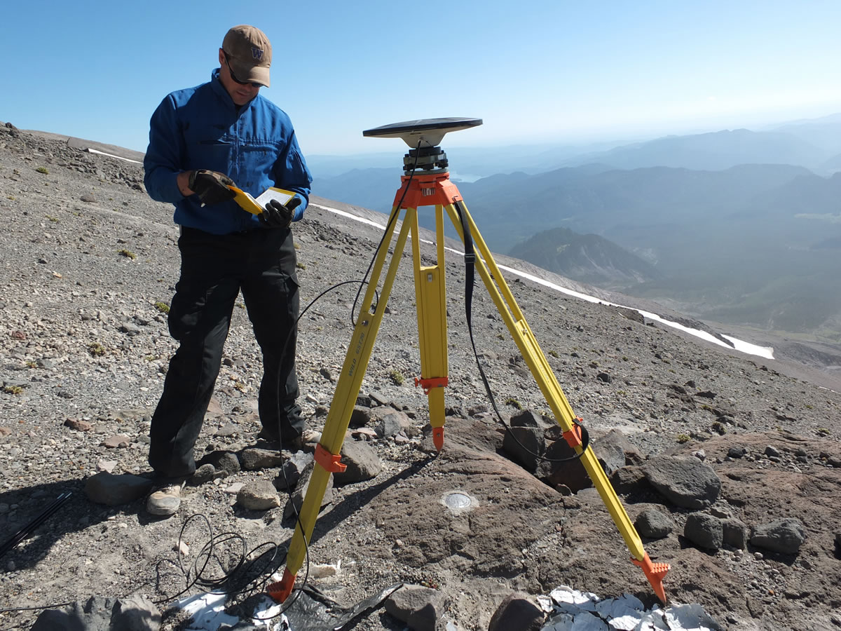 Ben Pauk, a geophysicist with the Vancouver-based Cascades Volcano Observatory, takes notes after setting up GPS equipment used to measure ground deformation on Mount St. Helens. The work is part of a series of upgrades and studies happening at the volcano this summer.
