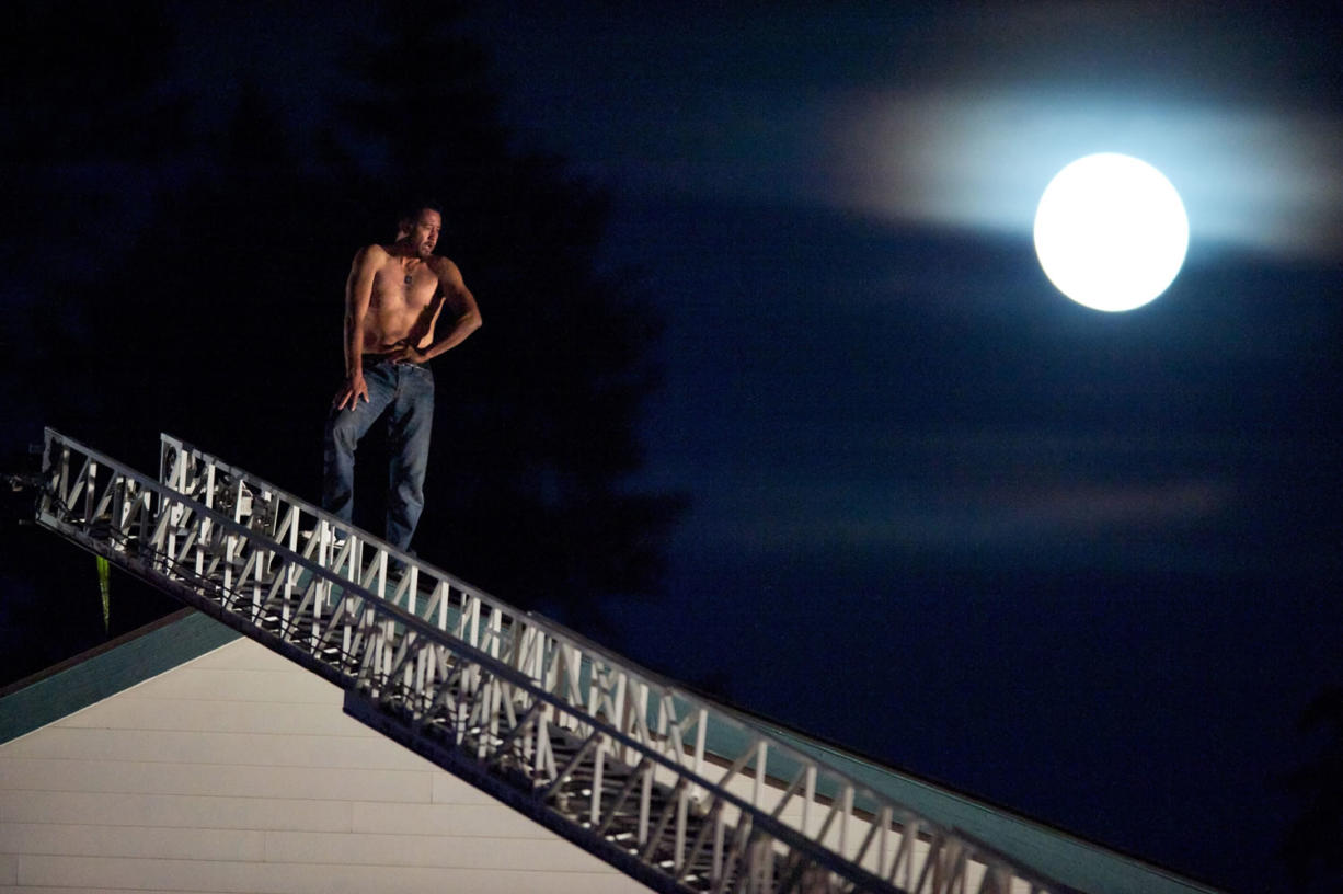 Angel M. Torres-Reyna, 41, of Vancouver, stands on the rooftop of the Quality Inn during a standoff with police after he  set fire to his hotel room on Saturday, Sept. 29, 2012. After  four hours on the roof, Torres-Reyna voluntarily climbed down a ladder and was taken into custody. He pleaded guilty to arson charges in the fire plus an earlier fire at his apartment on Jan. 7, 2013. (Zachary Kaufman/The Columbian)