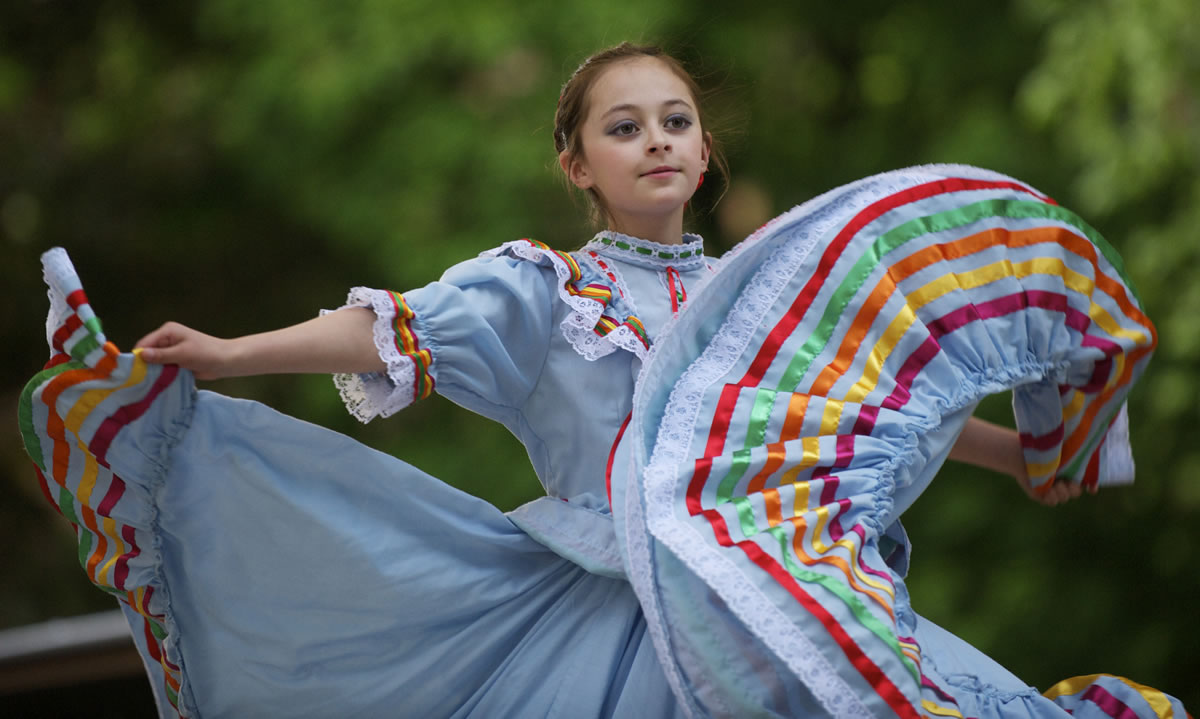 Marianna Cruz, 11, dances with a traditional Mexican dance group Wednesday during an immigration reform rally at Esther Short Park.