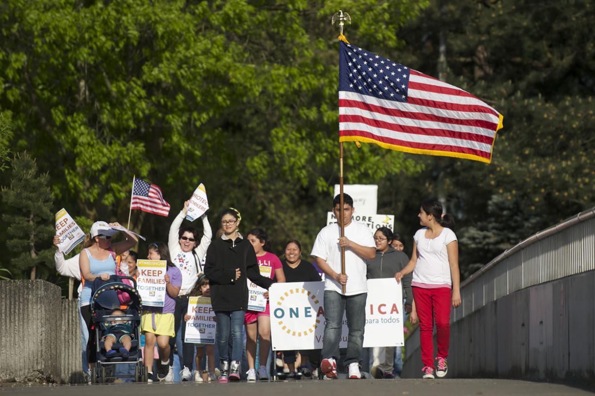 A group of immigration reform supporters marches Wednesday from U.S. Rep. Jaime Herrera Beutler's Vancouver office at the O.O.