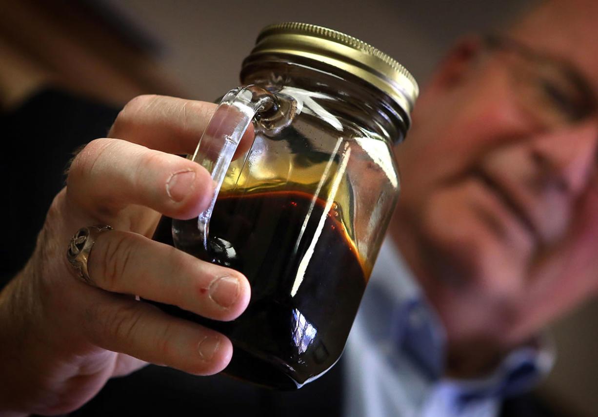 Williston, North Dakota Mayor E. Ward Koeser displays a jar containing Bakken crude oil, May 2, 2013. (Jim Gehrz/Minneapolis Star Tribune/MCT)