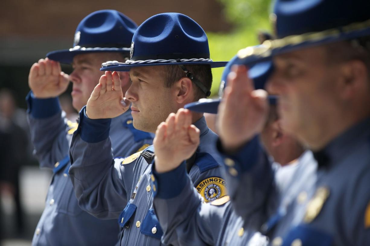 Washington State Patrol troopers salute during the national anthem.