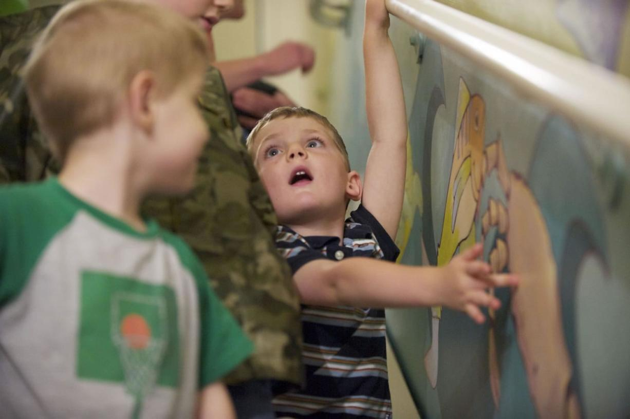 Logan Volk, 4, gets a hands-on look July 20 as Legacy Salmon Creek Hospital unveils a new mural, created by local artist Rebecca Anstine, in a stairwell used for pediatric rehab and physical therapy.