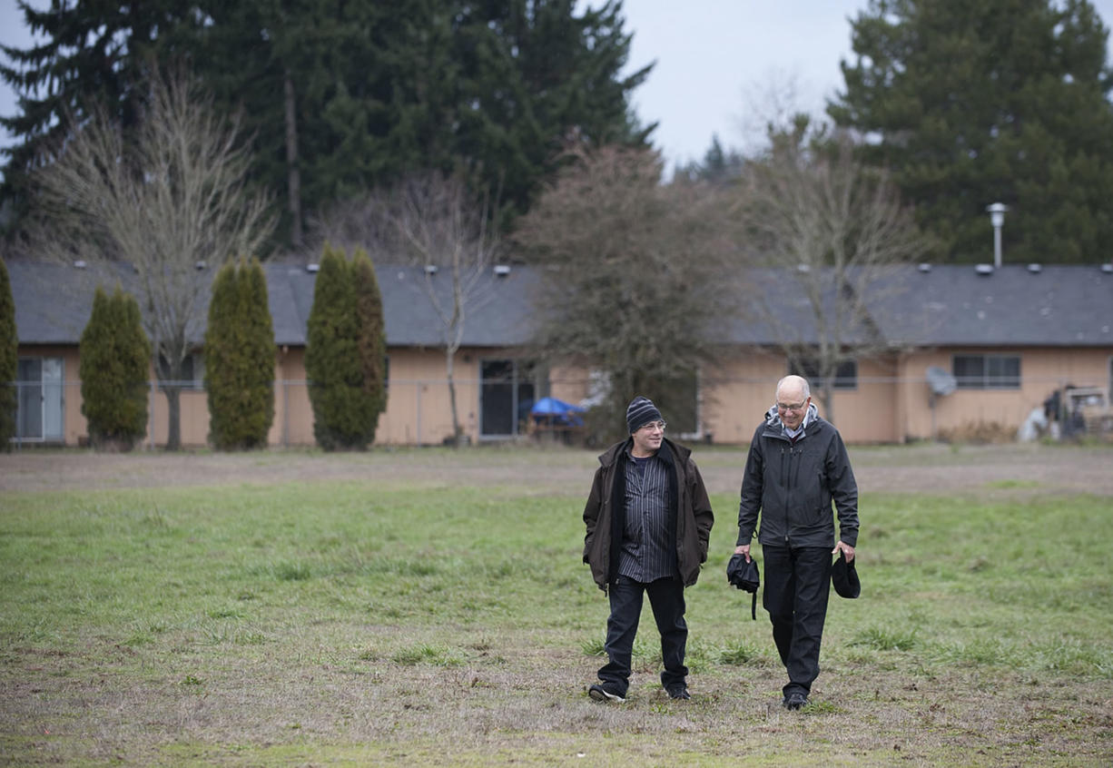 Adam Kravitz, left, founder of Outsiders Inn, strolls with Bill Ritchie of the Clark County Commission on Aging on Dec. 3 outside Safe Harbor Church of the Nazarene in Vancouver, where the Council for the Homeless had planned to build a village of 40 tiny houses for the homeless. Wednesday, the church backed out of the project, and organizers are looking for a new site.