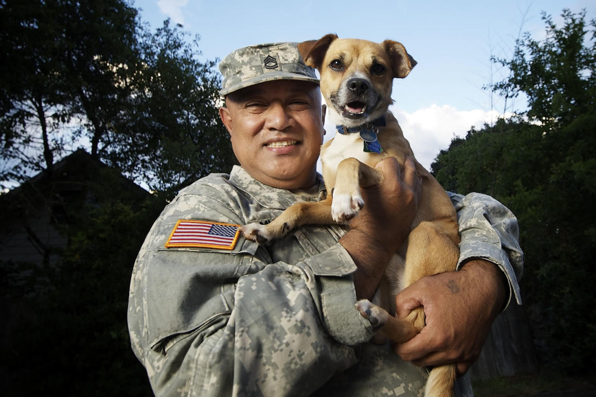 Sgt. 1st Class Bennett Muasau holds his wayward dog Brownie, who became somewhat of a celebrity Monday after getting rescued from the roof of an Orchards-area house just five blocks away.