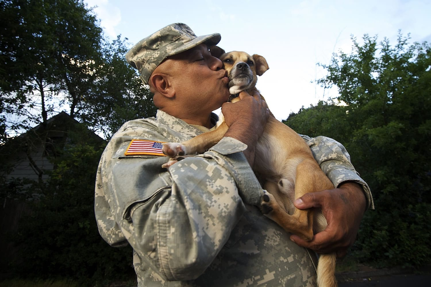 Sgt. 1st Class Bennett Muasau kisses his wayward dog Brownie, who became somewhat of a celebrity Monday after getting rescued from the roof of an Orchards-area house just five blocks away.