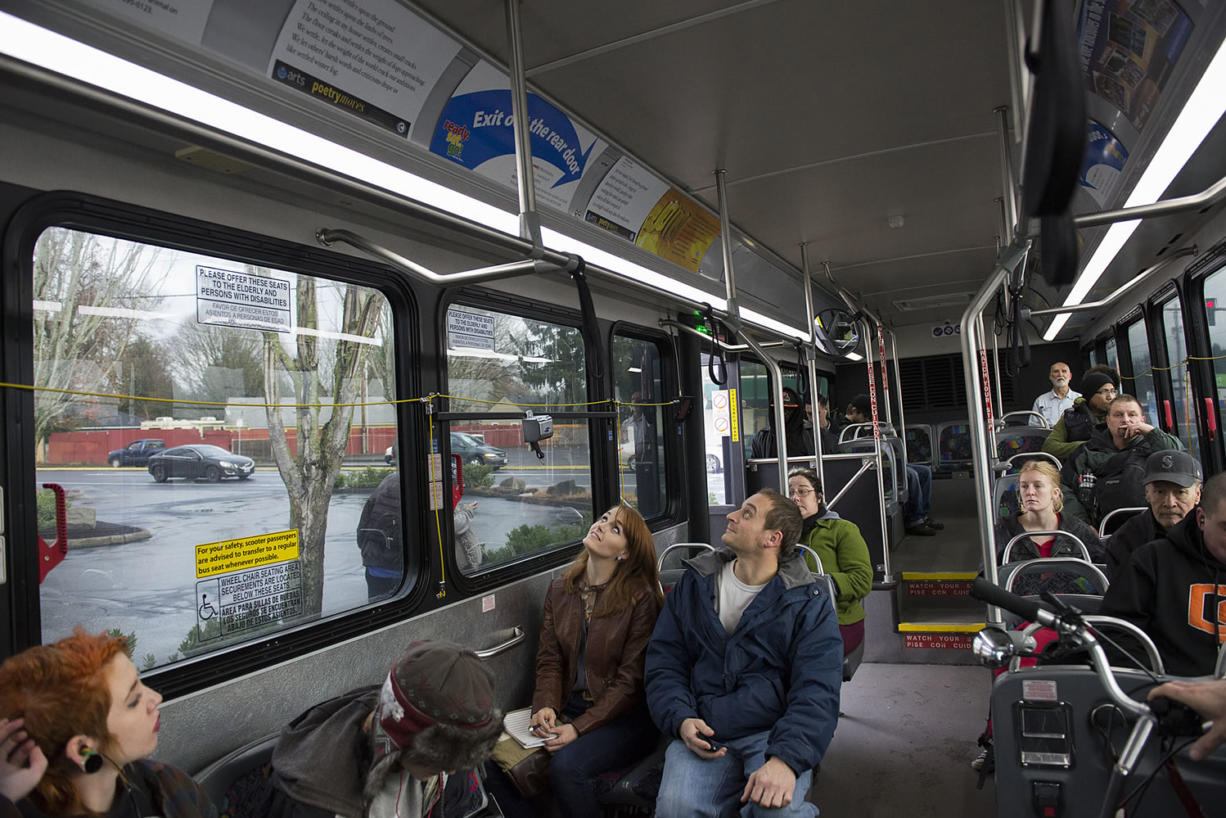 Poet Erin Iwata of Ridgefield, center in brown jacket, reads some moving poetry wtih Michael Atton of Vancouver aboard the no. 4 bus along Fourth Plain Boulevard on Dec. 14.