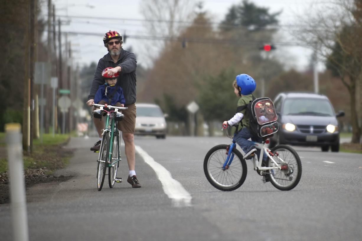 Paul Deming helps his son, Brian, 6, cross MacArthur Boulevard on March 13. Paul Deming and other cyclists have safety concerns along the corridor because of the large number of lanes and the speed of traffic. In the bike seat is Danny Deming, 10 months.