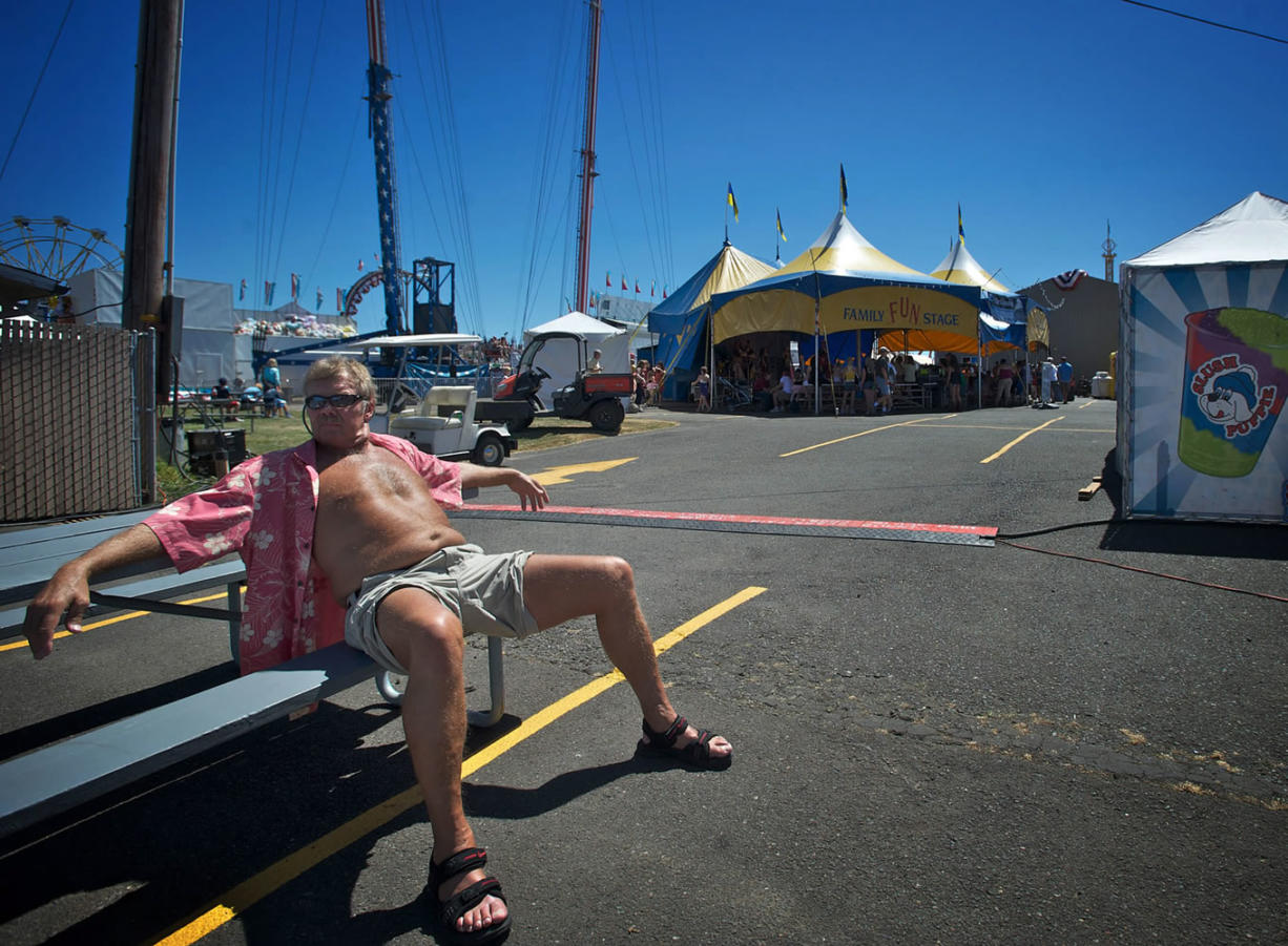 "Vancouver native Dennis Kostman, 64, soaks up the sun at the Clark County Fair on Saturday. Kostman says he enjoys the heat. ""I love it, because I know the rain is right around the corner."""