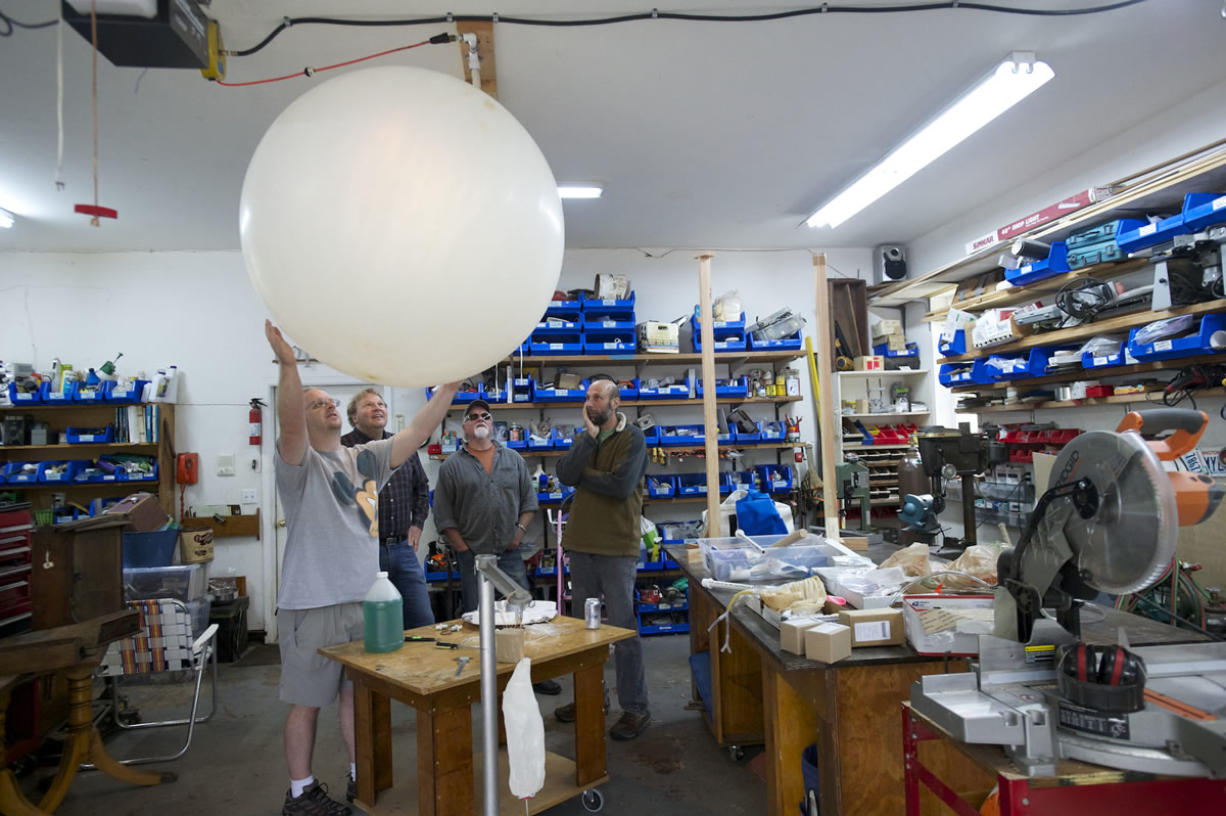 James Sutherland, from left, Kevin Cyrus, Rich Sutherland and Joe Barbera check out a helium-filled balloon that will be part of Sunday's unmanned test flight.