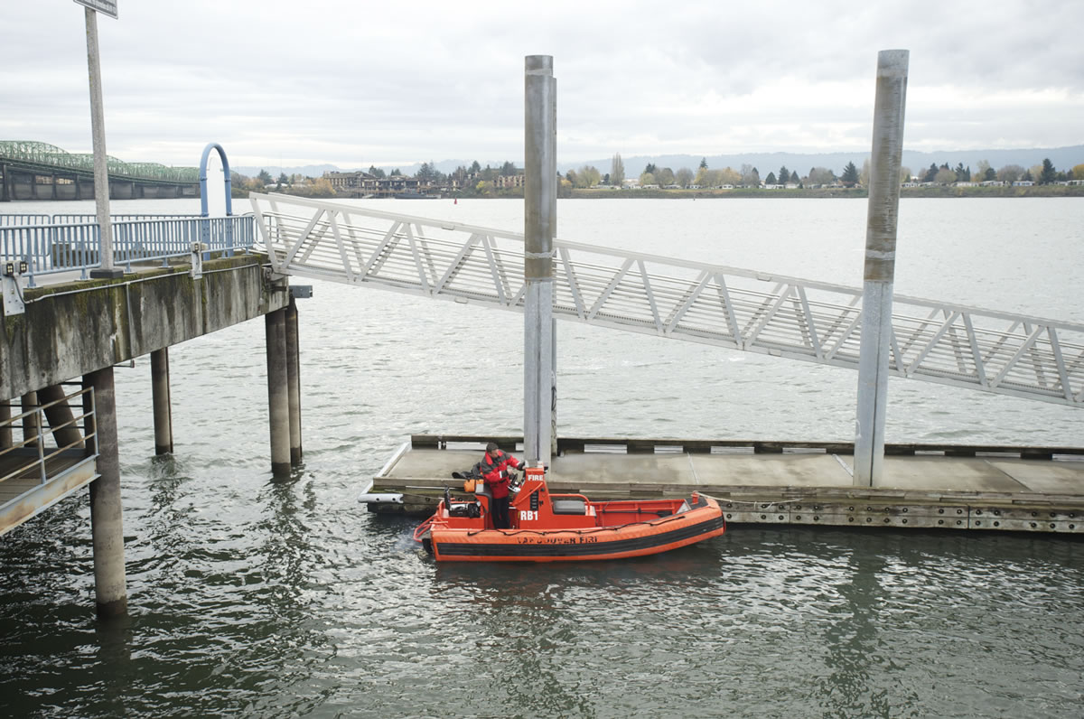 Vancouver firefighter Casey Holmes preps the department's boat, which was bought for $500 five years ago, for a media ride on the Columbia River on Nov. 29.
