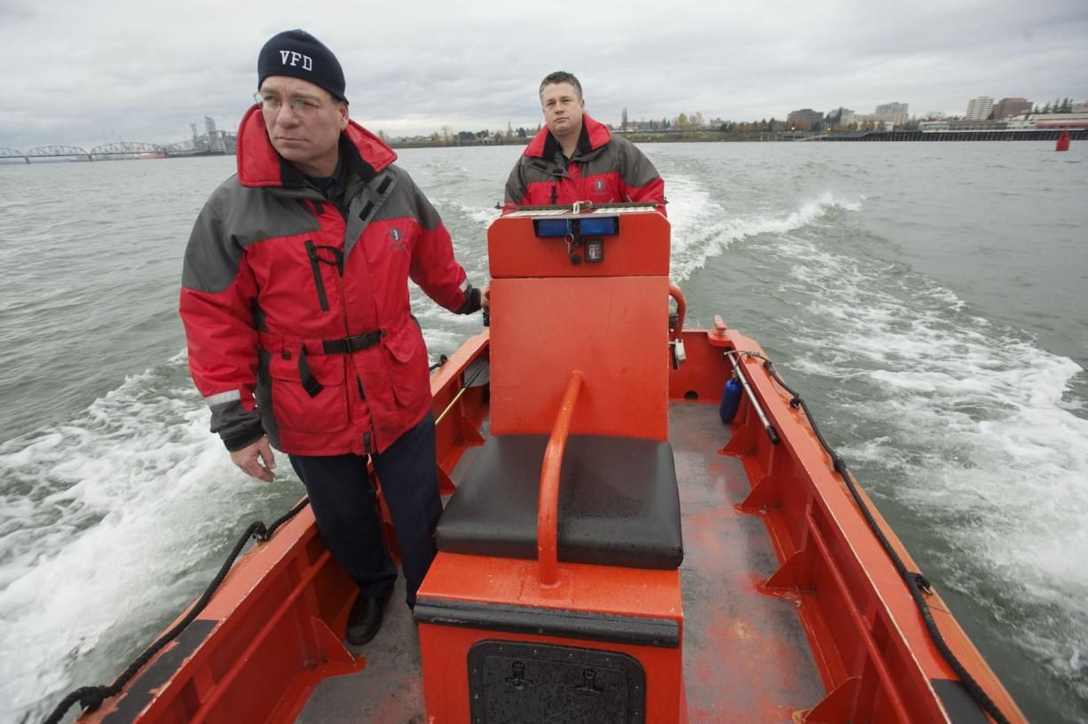 Vancouver Fire Department Captain Tom Coval, left, and firefighter Casey Holmes demonstrate the top speed of the department's boat on the Columbia River on Nov. 29. The boat maxes out at 20 miles per hour. Tonight, the Vancouver City Council will vote on whether to accept a federal grant for a Quick Response Vessel, which, unlike the department's boat, would actually have pumping capabilities.