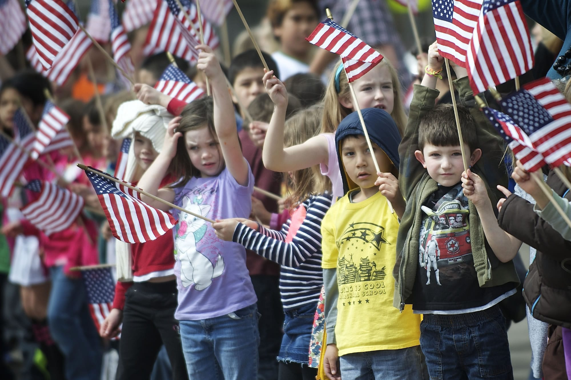 Students at Marshall Elementary School wave American flags as they say goodbye to retired U.S.
