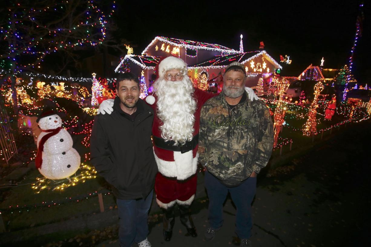Randy Peppers, from left, David Buffum (dressed as Santa) and Paul Lamb have a friendly competition to show who can put up the most elaborate Christmas decorations at their homes on Southeast Riveridge Drive.