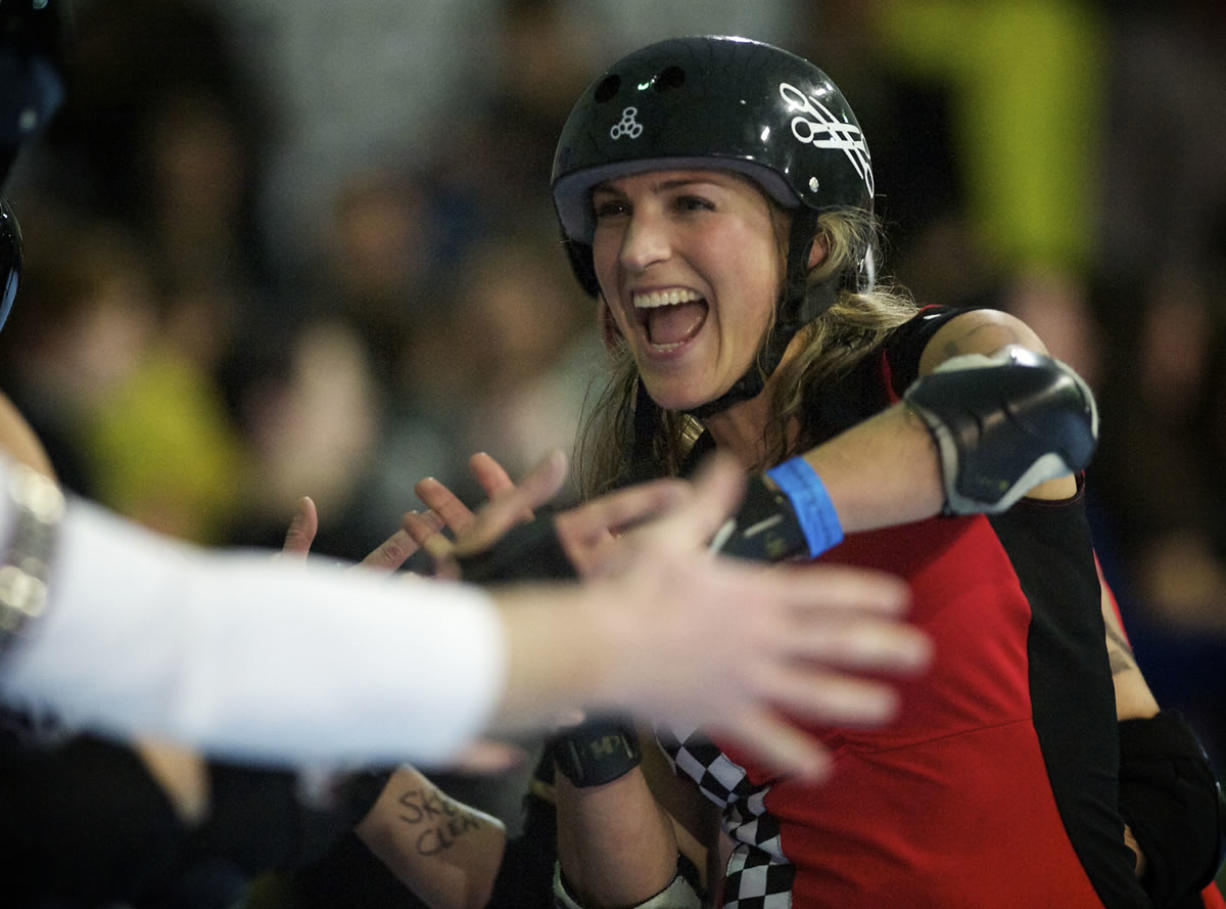 "Jessica ""Chestnutz"" Chestnut slaps hands with skaters after her team, the Break Neck Betties, loses a close match against the Guns N Rollers at the Hangar at Oaks Park on March 23."