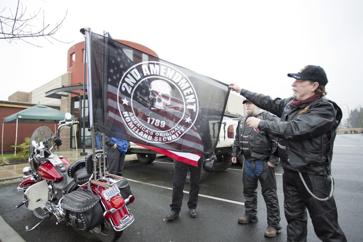 Barry Smith, a Patriot Guard rider from Rainier, Ore., shows the Second Amendment flag that hangs on the back of a motorcycle outside Coffee Villa in Vancouver, where gun supporters gathered for an open carry event Saturday.
