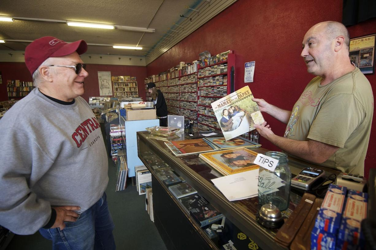 Brian Wassman, right, owner of Everybody's Music, explains the history of a record album's photo cover to customer Chip Bedord at the record store in Uptown Village he opened in 1992.