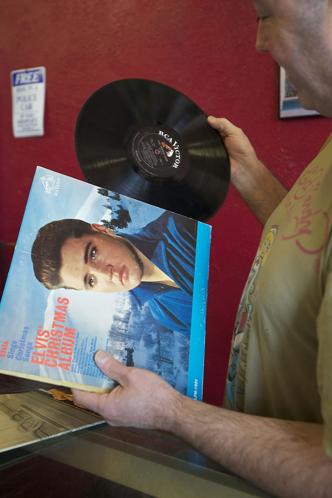 Brian Wassman checks the condition of an Elvis Presley album at Everybody's Music, an Uptown Village record store Wassman has listed for sale after owning and operating it for nearly 22 years.