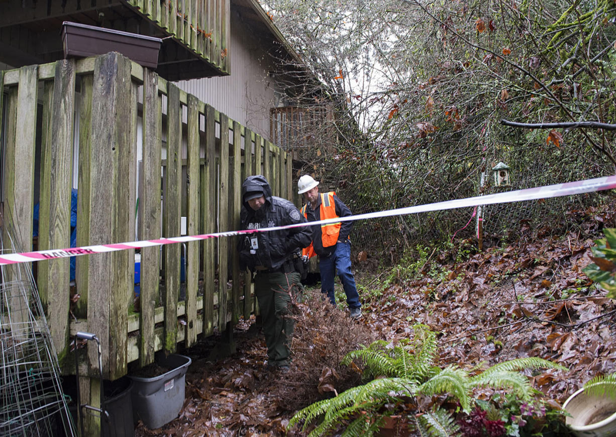 Deputy Albin Boyse, left, and Ken Price of the Clark County Public Works Department investigate the scene of a mudslide Monday afternoon, Dec. 7, 2015 at Greenway Estates in Hazel Dell. (Amanda Cowan/The Columbian)