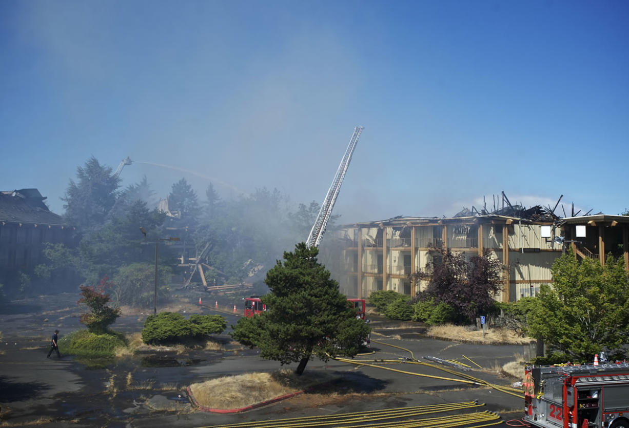 Portland firefighters dump water on the vacant Thunderbird Hotel on Hayden Island after a fire started early Sunday morning.